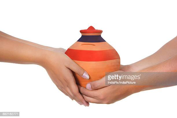 Cropped image of couple holding piggy bank against white background