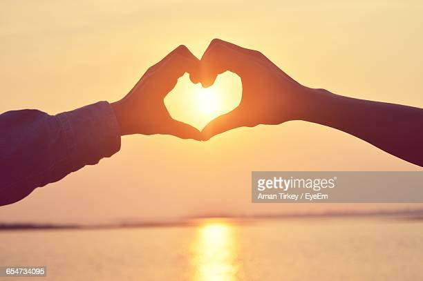 Cropped Image Of Couple Making Heart Shape With Hands By Sea Against Sky
