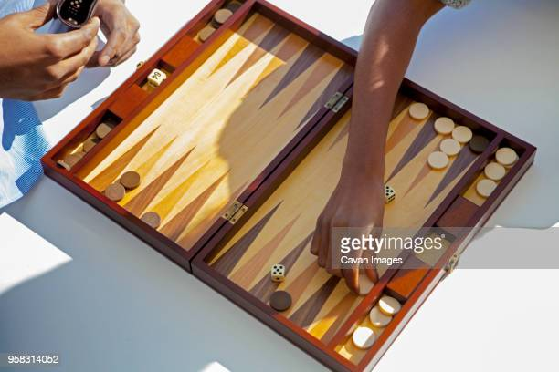 cropped image of couple playing backgammon at home - backgammon stock pictures, royalty-free photos & images