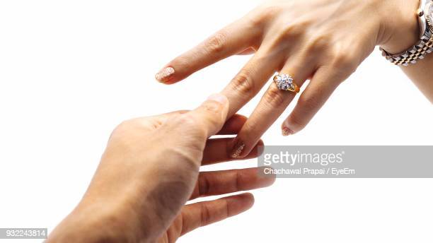 cropped image of couple with holding hands against white background - man holding engagement ring stock photos and pictures