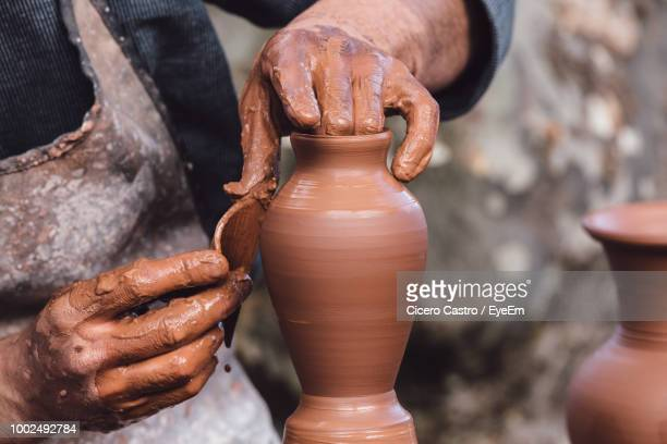 cropped image of craftsperson shaping urn - turning stock photos and pictures