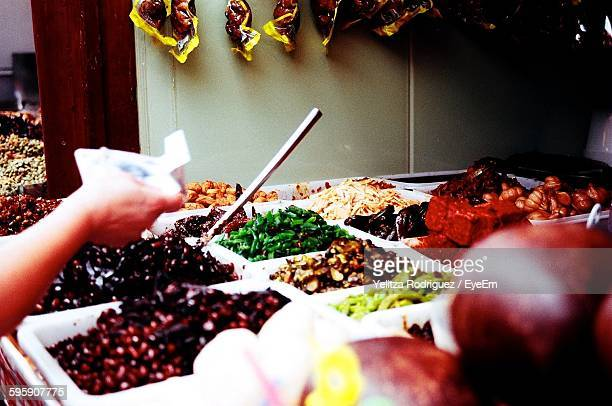 Cropped Image Of Customer Holding Currency Note By Variety Of Spices For Sale In Market