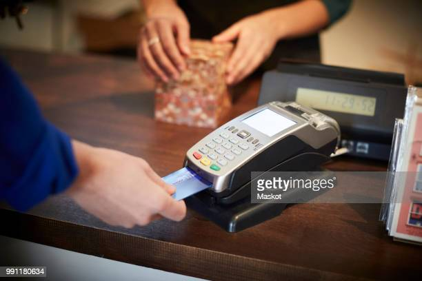 Cropped image of customer paying through credit card at checkout counter