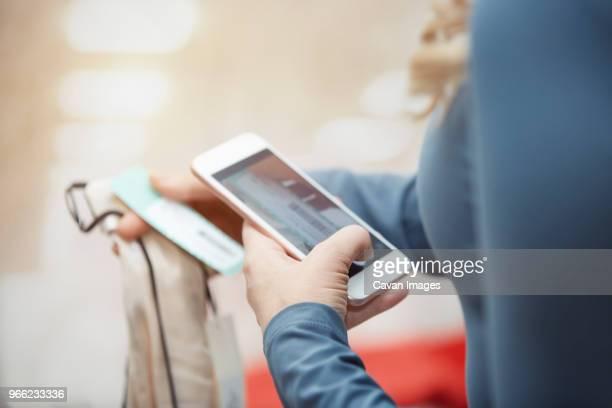 cropped image of customer photographing dress with smart phone in boutique - prezzo messaggio foto e immagini stock