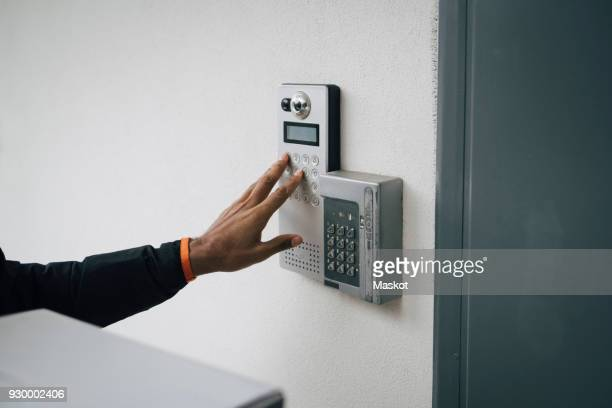 cropped image of delivery man ringing intercom on wall - intercom stock pictures, royalty-free photos & images