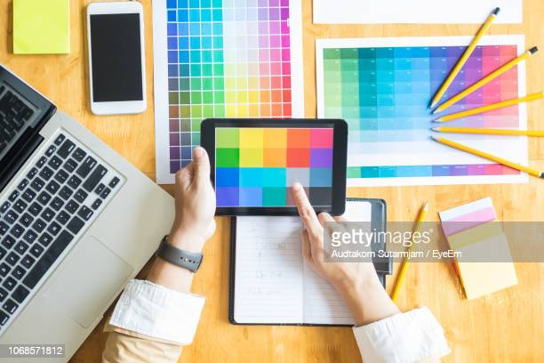 cropped image of design professional choosing color samples on digital tablet - デザイナー ストックフォトと画像