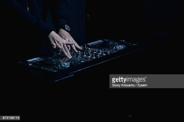 Cropped Image Of Dj Mixing Music On Turntable