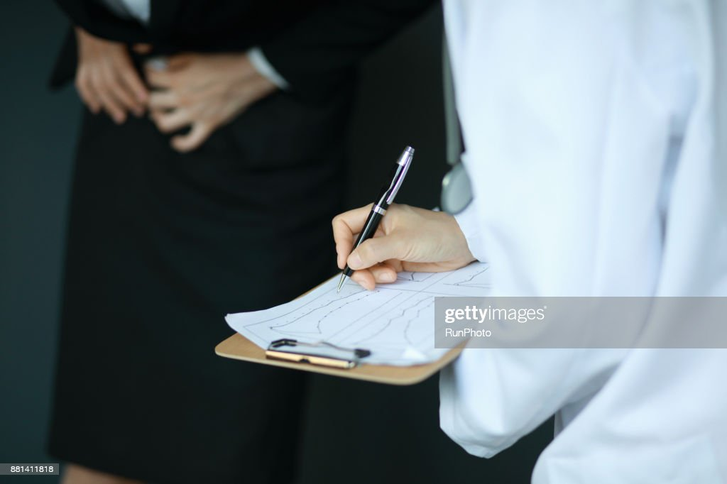 Cropped image of doctor examining patient with stomachache : Stock Photo