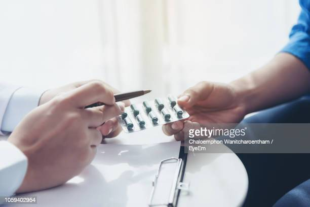 cropped image of doctor explaining pills to patient in hospital - pill blister stock pictures, royalty-free photos & images
