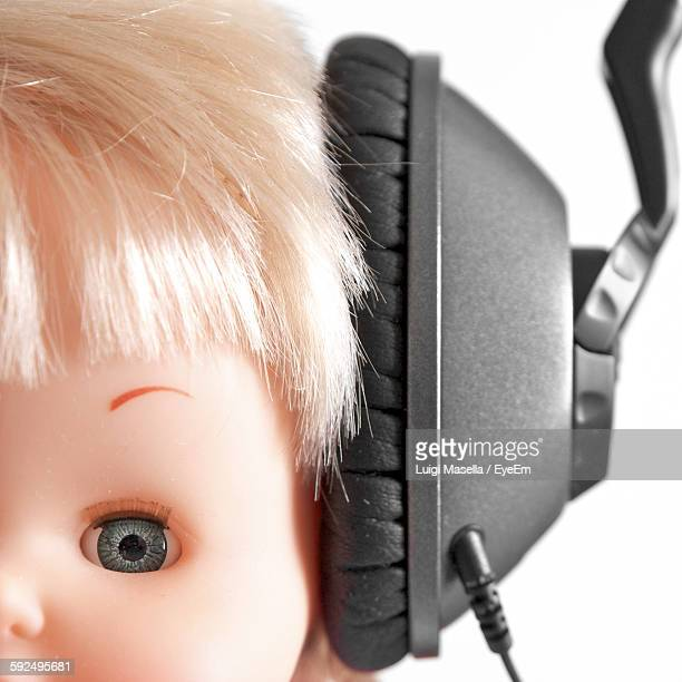 Cropped Image Of Doll With Headphones Against White Background