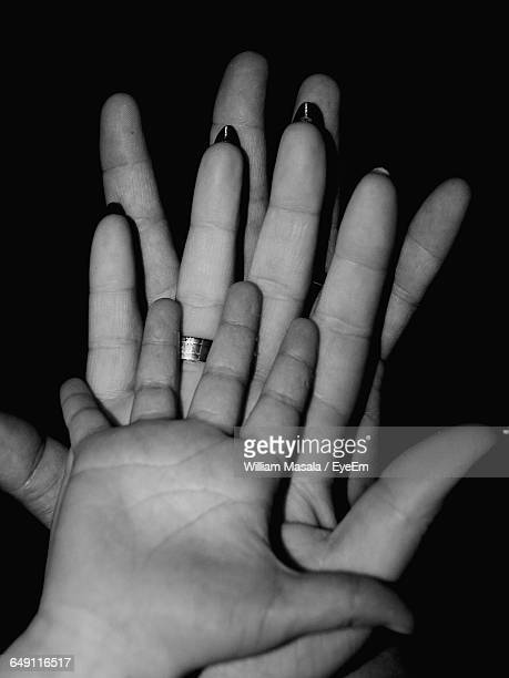 Cropped Image Of Family Hands Against Black Background