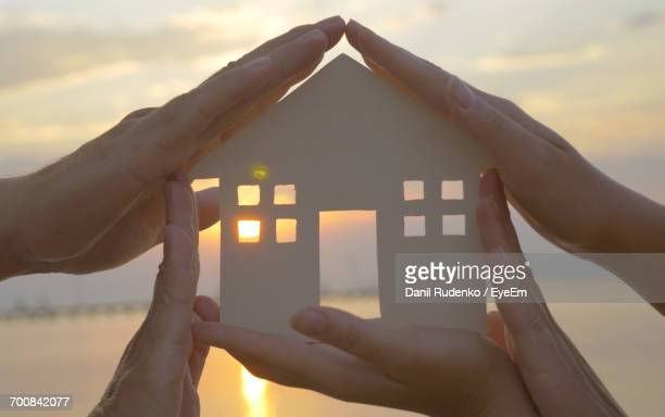 Cropped Image Of Family Holding House Shape At Beach During Sunset
