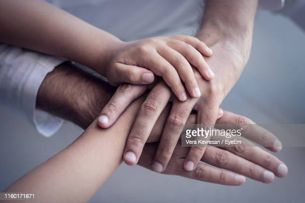 cropped image of family stacking hands - mani incrociate foto e immagini stock