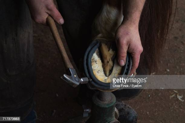 Cropped Image Of Farrier Hammering Horseshoe In Workshop
