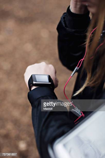 Cropped image of female athlete checking fitness tracker in forest