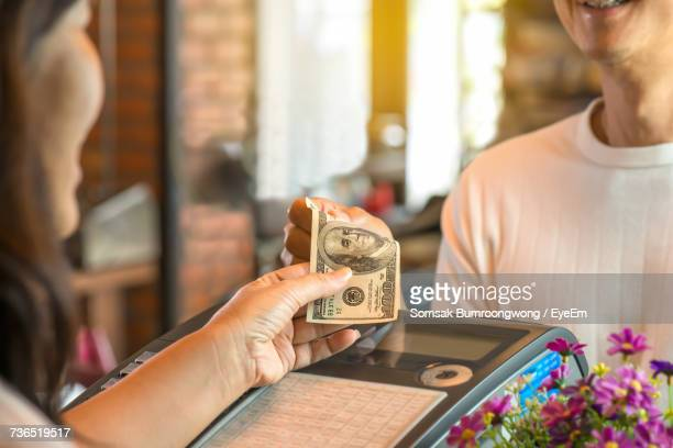 Cropped Image Of Female Cashier Receiving Paper Currency From Customer Over Cash Machine At Restaurant
