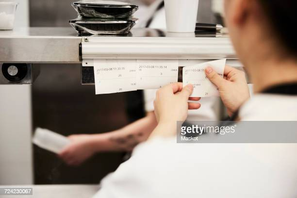 Cropped image of female chef reading order tickets in commercial kitchen