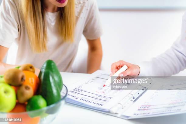 cropped image of female doctor explaining to patient in hospital - speisen und getränke stock-fotos und bilder