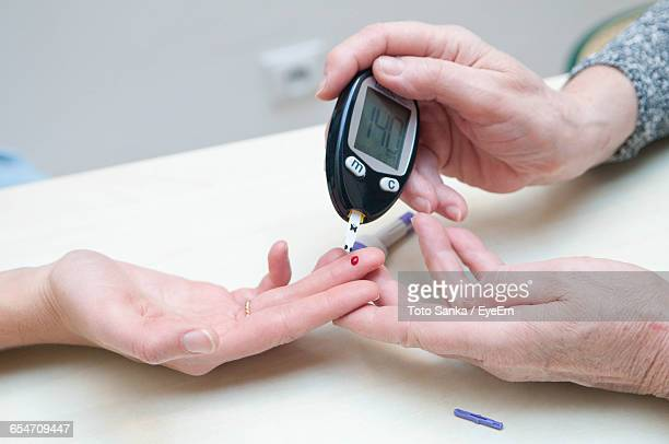 Cropped Image Of Female Doctor Performing Diabetes Test On Patient At Hospital