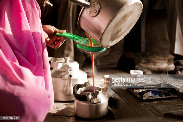 Cropped image of female vendor pouring hot streaming chai in kettle