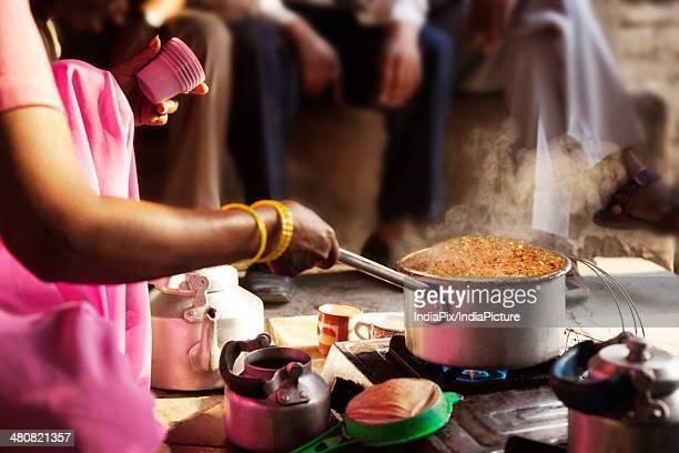 Cropped image of female vendor preparing chai at market stall
