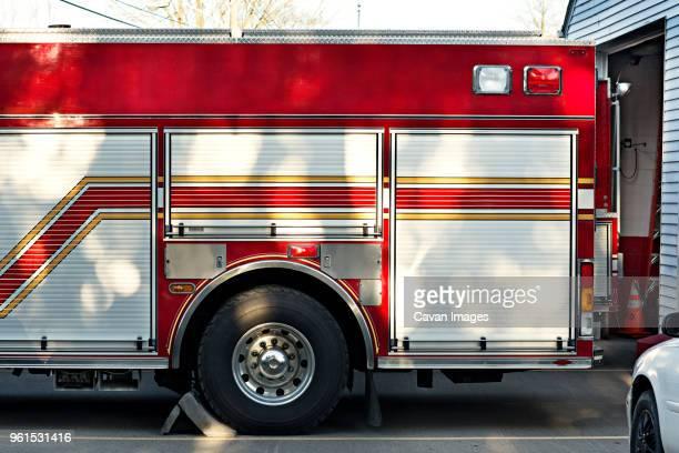 cropped image of fire engine outside fire station - carro de bombeiro - fotografias e filmes do acervo
