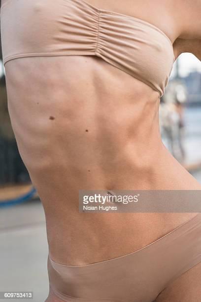 cropped image of fit woman stomach - ヌードカラー ストックフォトと画像