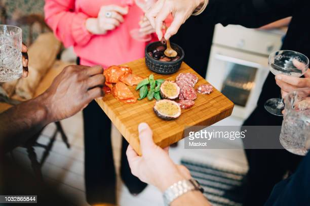 cropped image of friends enjoying food and drinks at dinner party - serving tray stock pictures, royalty-free photos & images