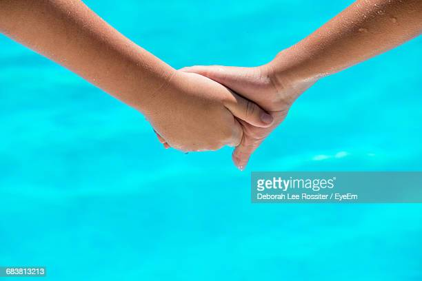 Cropped Image Of Friends Holding Hands Against Turquoise Swimming Pool