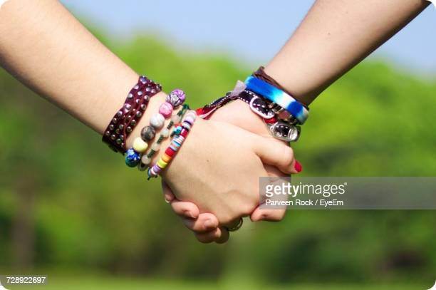 cropped image of friends holding hands - bracelet stock pictures, royalty-free photos & images