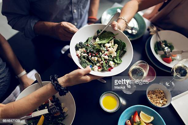 cropped image of friends holding salad bowl at table - nut food stock photos and pictures
