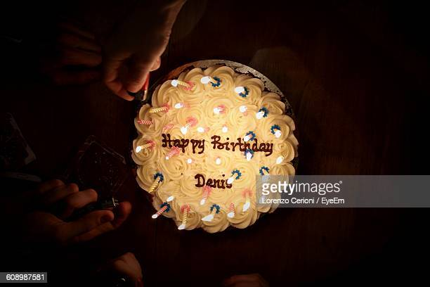 cropped image of friends lighting birthday candles - birthday cake stock photos and pictures