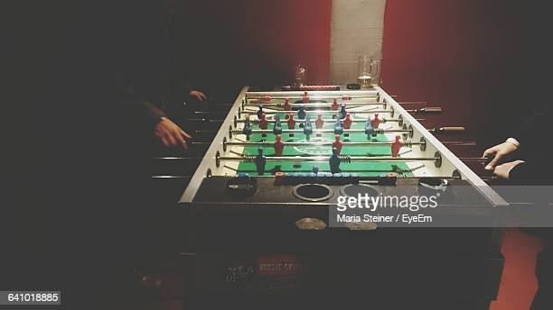 Cropped Image Of Friends Playing Foosball