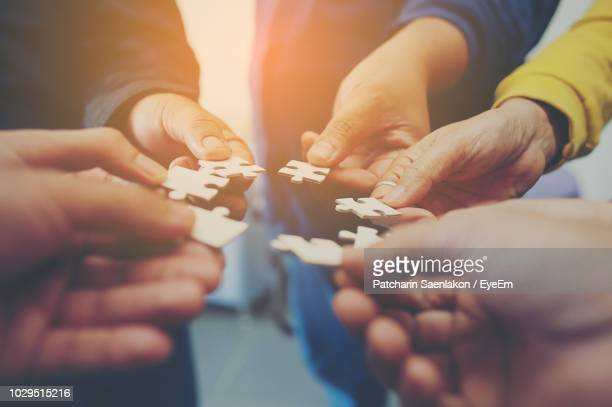 cropped image of friends playing jigsaw puzzle - puzzle stock pictures, royalty-free photos & images
