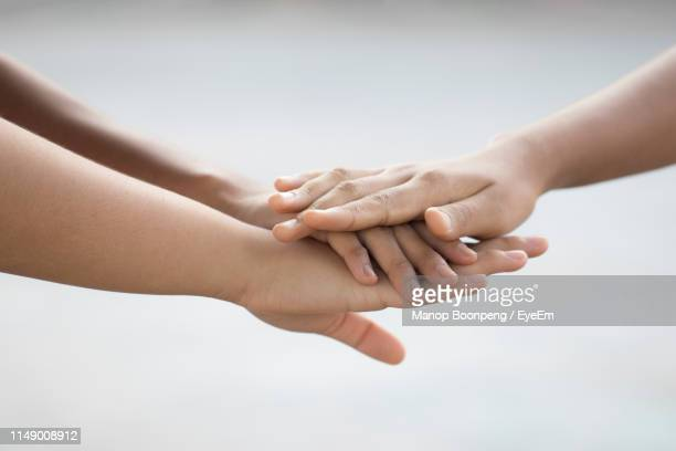 cropped image of friends stacking hands - 積み重ねる ストックフォトと画像