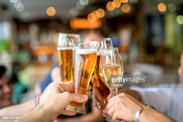 cropped image of friends toasting drinks in celebration. - bere foto e immagini stock