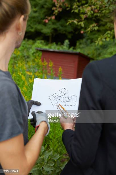 cropped image of garden architects analyzing blueprint - garden drawing stock pictures, royalty-free photos & images