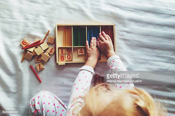 Cropped Image Of Girl Counting Sticks On Bed At Home