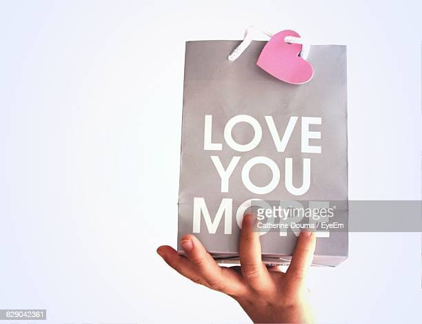 Cropped Image Of Girl Holding Shopping Bag With Text Message Against White Background