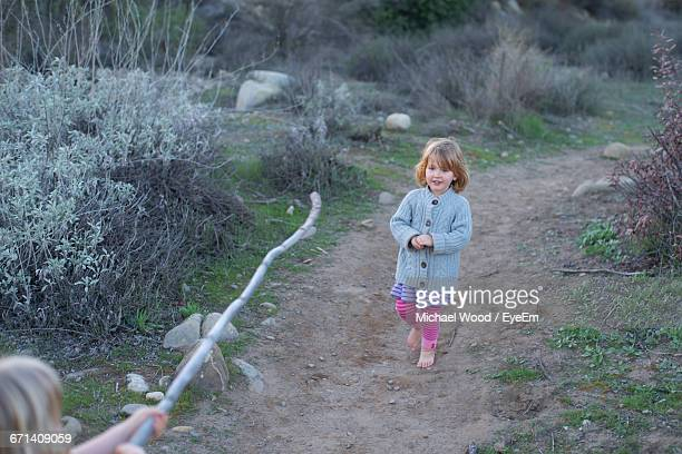 Cropped Image Of Girl Holding Stick Towards Sister Walking On Pathway