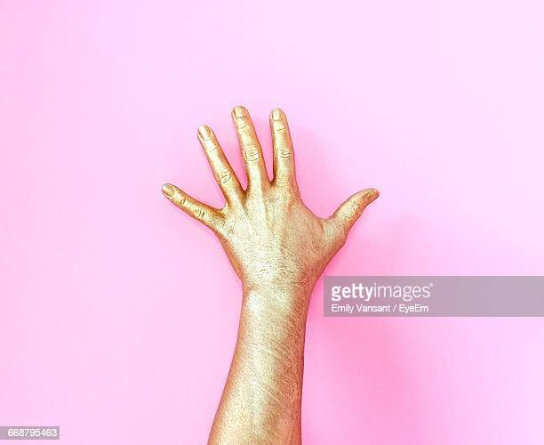 cropped image of gold painted hand against pink background - dedo humano fotografías e imágenes de stock