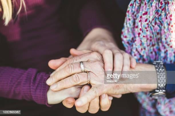cropped image of granddaughter and grandmother holding hands - begeleid wonen stockfoto's en -beelden