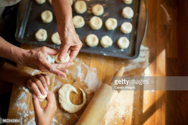 cropped image of granddaughter and grandmother making cookies at kitchen counter - innocence stock pictures, royalty-free photos & images