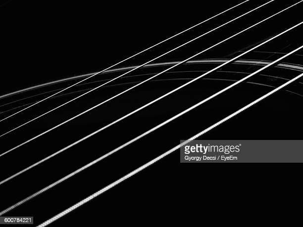 cropped image of guitar strings against black background - stringed instrument stock pictures, royalty-free photos & images