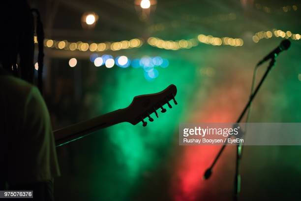 cropped image of guitarist performing at concert - microphone stand stock photos and pictures