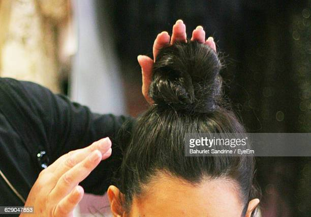 Cropped Image Of Hairdresser Hands Making Hair Bun Of Woman