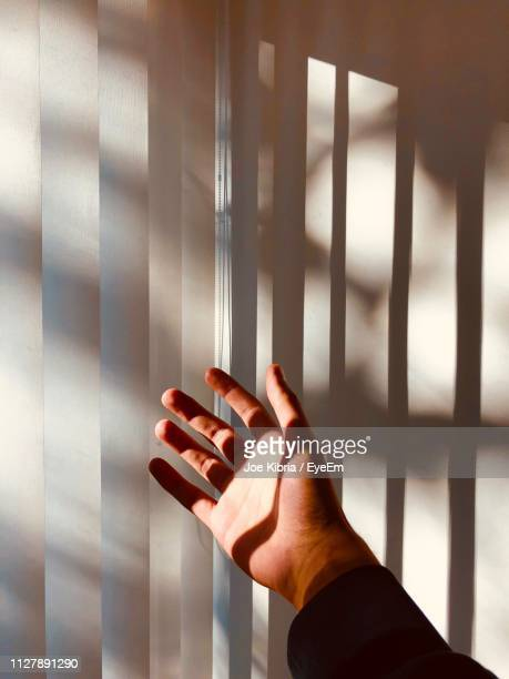 cropped image of hand against blinds at home - vertical stock pictures, royalty-free photos & images