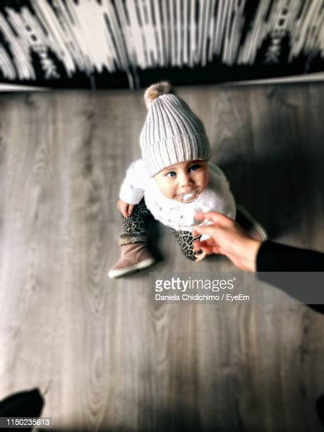 cropped image of hand by cute baby sitting on floor at home - one baby girl only stock pictures, royalty-free photos & images