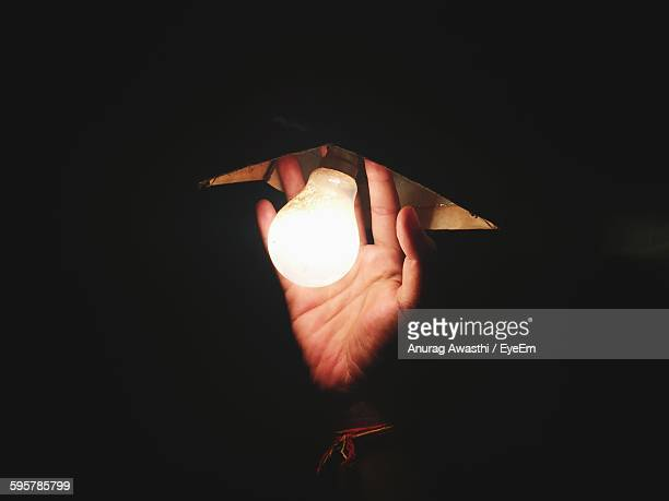 Cropped Image Of Hand By Illuminated Light Bulb
