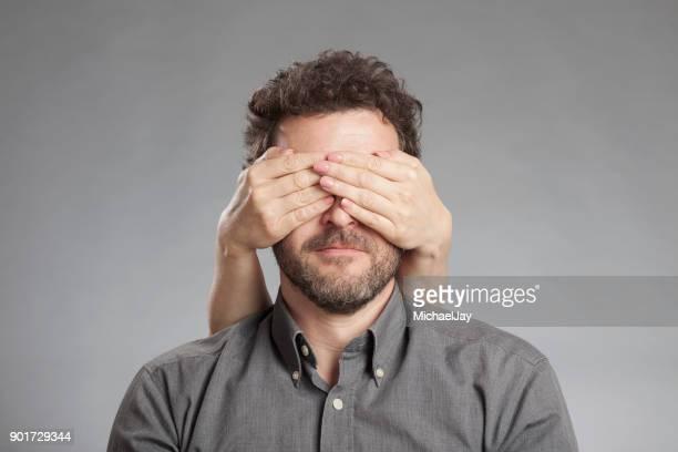 cropped image of hand covering man eyes against white background - augen zuhalten stock-fotos und bilder